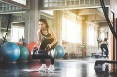 A mulher forte no sportswear faz o treinamento do peso dos exercícios no gym imagem de stock royalty free