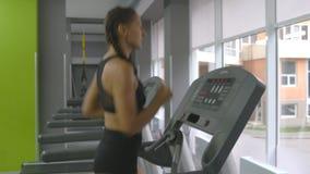 Mulher forte nova com corpo perfeito da aptidão no sportswear que corre na escada rolante no gym Menina que exercita durante card video estoque