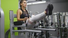 Mulher forte nova com o corpo perfeito da aptidão no sportswear que exercita abdominals no gym Treinamento da menina - pés de lev imagens de stock
