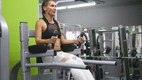 Mulher forte nova com o corpo perfeito da aptidão no sportswear que exercita abdominals no gym Treinamento da menina - pés de lev video estoque