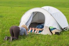 A mulher fotografa um menino e uma menina na barraca do turista Imagem de Stock Royalty Free