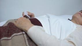 Mulher fraca no botão de empurrão do leito do enfermo para tomar a dose da medicina para aliviar a dor vídeos de arquivo