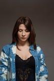 Mulher Freckled que veste uma camisa de brim que olha para baixo Foto de Stock