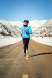 Mulher fria do inverno que corre na estrada Fotos de Stock Royalty Free
