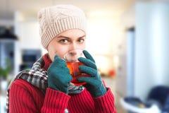 Mulher fria doente que bebe o chá quente dentro em casa imagem de stock royalty free