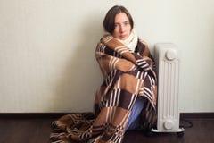 Mulher fria nova envolvida na cobertura que senta-se perto de Heater At Home elétrica foto de stock