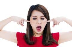 Mulher frustrante com os dedos em suas orelhas fotografia de stock royalty free
