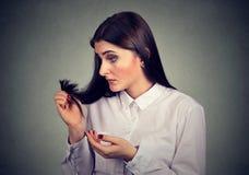 A mulher frustrante infeliz surpreendeu-a é cabelo perdedor, extremidades rachadas observadas Fotografia de Stock