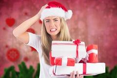 Mulher frustrante na pilha da terra arrendada do chapéu de Santa de presentes Fotos de Stock