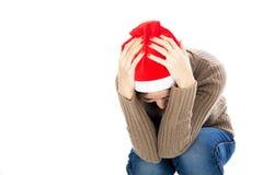 Mulher frustrante no chapéu de Santa que senta-se com sua cabeça em suas mãos fotografia de stock