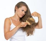Mulher frustrante que olha em extremidades do cabelo Fotografia de Stock Royalty Free