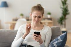 Mulher frustrante que olha o smartphone que senta-se no sofá fotografia de stock