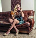 Mulher furada bonita que telefona ao assento no sofá Fotografia de Stock