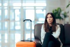 Mulher furada com a mala de viagem na sala de espera do aeroporto foto de stock