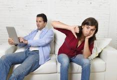 Mulher furada e frustrada ignorado quando marido ou noivo do viciado do Internet que usa trabalhos em rede digitais da tabuleta imagem de stock royalty free