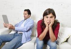 Mulher furada e frustrada ignorado quando marido ou noivo do viciado do Internet que usa trabalhos em rede digitais da tabuleta fotos de stock