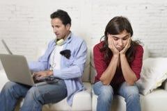 Mulher furada e frustrada ignorado quando marido ou noivo do viciado do Internet que usa trabalhos em rede digitais da tabuleta imagem de stock