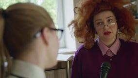 Mulher furada engraçada na peruca vermelha que dá a entrevista no microfone video estoque