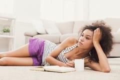 Mulher furada pensativa nova com livro fotografia de stock royalty free