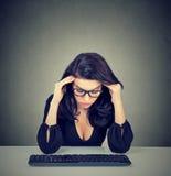 Mulher furada sobrecarregado que senta-se na mesa na frente de seu computador que olha para baixo fotografia de stock royalty free