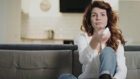 Mulher furando que verifica os canais de televisão na cozinha aberta Menina sonolento que desliga a tevê video estoque