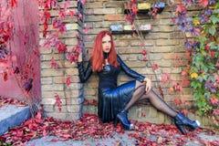 Mulher gótico principal vermelha nova que senta-se na parte inferior da parede de tijolo cercada pelas folhas de outono e por vid fotografia de stock