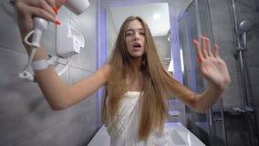 Mulher glamourosa com um lindo cabelo comprido em uma toalha gosta da diversão no banheiro posando na câmera, dançando ativamente vídeos de arquivo