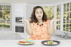 A mulher gorda confusa come na cozinha Foto de Stock
