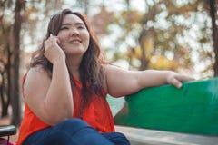 Mulher gorda feliz que usa o telefone celular Foto de Stock