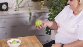 Mulher gorda que escolhe entre a maçã e o hamburguer Dieta e saudável filme