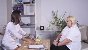 Mulher gorda que escolhe entre a maçã e o hamburguer Dieta e saudável vídeos de arquivo