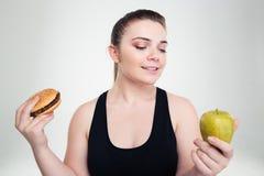 Mulher gorda que escolhe entre o hamburguer ou a maçã imagens de stock