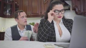 Mulher gorda segura bonita nova do retrato que trabalha com o portátil na tabela Um homem novo tímido que pede mais dinheiro e vídeos de arquivo