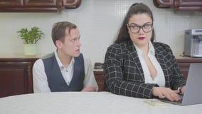 Mulher gorda segura nova do retrato nos vidros na tabela na cozinha que trabalha com portátil Pedir tímida do homem novo video estoque