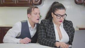 Mulher gorda segura nova na tabela que trabalha com portátil Um homem novo tímido que tenta olhar atrás de seu ombro vídeos de arquivo