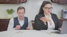 Mulher gorda segura nova na tabela que trabalha com portátil Um homem novo tímido toca em seu ombro e estende a mão video estoque