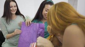 Mulher grávida caucasiana a receber presentes dos seus dois amigos Três meninas se preparando para o nascimento de uma criança filme
