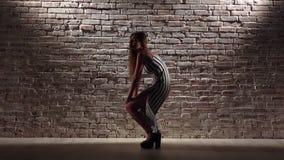A mulher graciosa nos saltos altos dança o twerk contra uma parede de tijolo Movimento lento video estoque