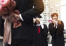 A mulher graduada dos graduados sorri e está feliz após a graduação fotos de stock