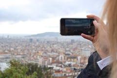 A mulher grava um vídeo que negligencia uma grande cidade Imagens de Stock Royalty Free