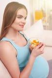 A mulher gravida alegre está comendo a salada saudável imagem de stock royalty free