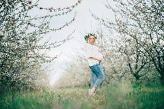 Mulher gravida alegre nova bonita na grinalda das flores na barriga tocante principal ao andar no jardim da árvore da mola beleza imagem de stock