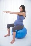 Mulher gravida asiática bonita que faz o exercício com uma bola suíça, imagens de stock royalty free