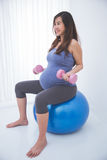 Mulher gravida asiática bonita que faz o exersice em uma bola da ioga, ho Imagem de Stock Royalty Free