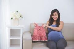 Mulher gravida asiática bonita que senta-se em um sofá que guarda um bonito Imagens de Stock
