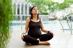 A mulher gravida asiática meditate imagem de stock royalty free