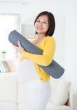 Mulher gravida asiática que guardara a esteira da ioga foto de stock