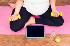 Mulher gravida ativa com pesos que exercita com cours video Fotos de Stock Royalty Free