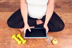 Mulher gravida ativa com pesos que exercita com cours video Imagens de Stock