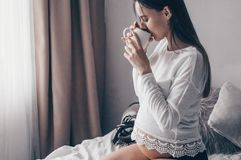 A mulher gravida atrativa bebe o chá na cama Chá bebendo que olha através de uma janela em casa Últimos meses da gravidez foto de stock royalty free